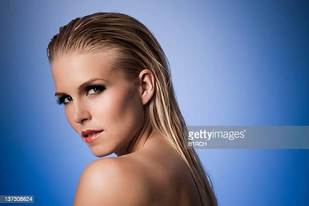 Sexy mannequin avec les cheveux mouillés contre un fond bleu.