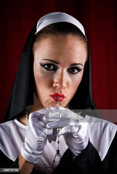 sexy Nonne mit einem Rosenkranz in mouth