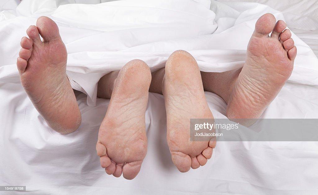 sexy senior feet in bed : Stock Photo
