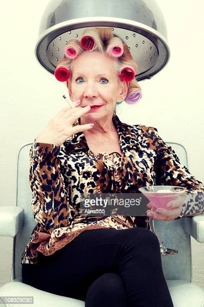 Sexy senior woman with attitude  wearing rollers in beauty salon