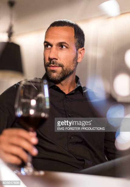sexy single man enjoying his red wine on a table while flirting in a hotel lounge