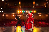 Two beautiful feminine dancers with different dance styles, performing a duet on stage.