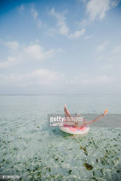 Sexy woman floating on water and have cocktail time in ocean, Maldives