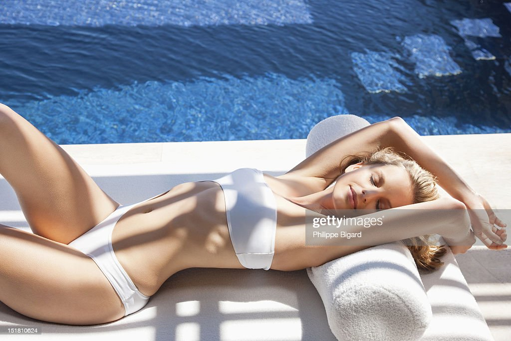 Sexy woman in bikini laying on lounge chair at poolside : Stock Photo