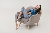 beautiful smiling sexy woman in denim clothes sitting on armchair and looking away isolated on grey