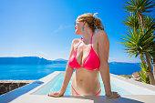 Sexy woman in pink bikini in swimming pool looking at sea