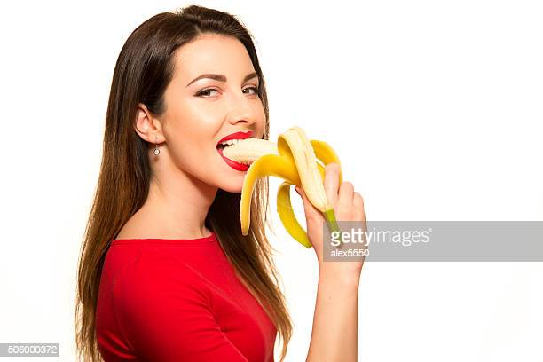 Sexy Woman in Red Clothes Eating Banana on White Background Isolated  Smiling