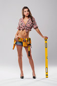 Sexy woman leaning on yellow spirit level