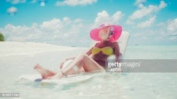 Sexy woman sitting in shallow water, Maldives