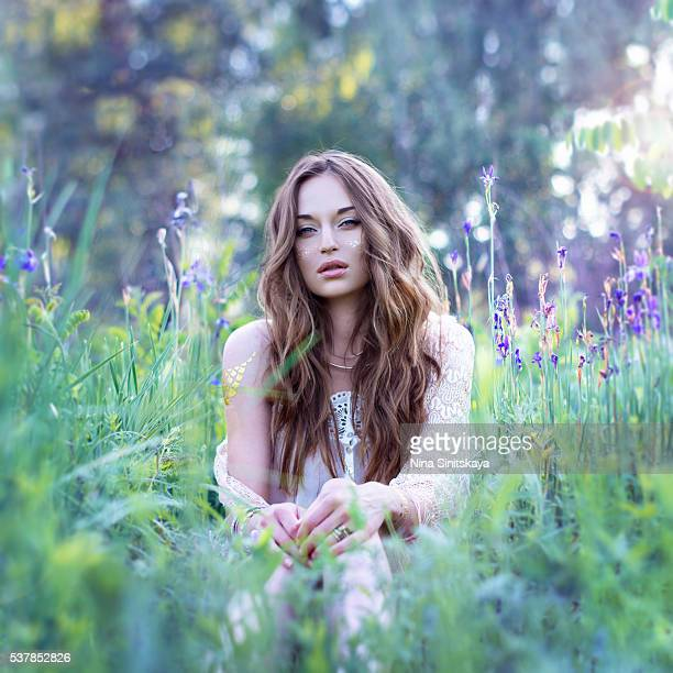 Sexy woman with long wavy hair in summer outfit sitting among flowers