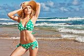 Sexy Young Blonde Woman in Green Polka-dot Bikini and Hat