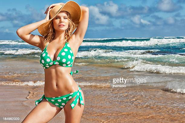 Sexy Young Blonde Woman in Green Polka-dot Bikini and Hat