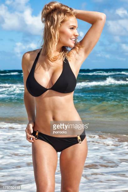 Sexy Young Blonde Woman on Beach in Black Bikini