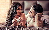 Sexy young couple is looking at each other and smiling while lying on bed at home, woman is holding a condom