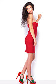 Full length picture of a sexy young lady leaning her hand on a white wall while looking away from the camera.