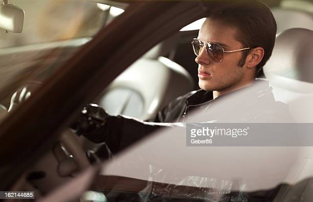 Sexy young man driving car