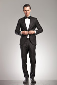 sexy young man in tuxedo and bowtie buttoning his suit on grey studio background, full body picture