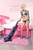 Sexy young tattooed woman in bikini vacuuming bedroom