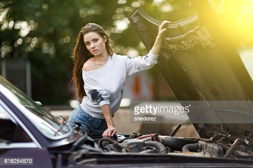 Sexy young woman posing with open hood of her car : Foto de stock