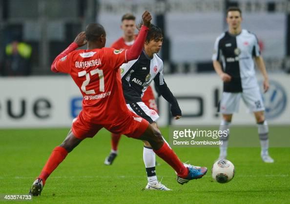 Seyi Olajengbesi of SV Sandhausen challenges Takashi Inui of Eintracht Frankfurt during the DFB Cup match between Eintracht Frankfurt and SV...
