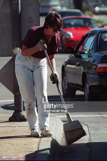 SFLadies5bv11–2/RESEDA –– Reseda homeowner Barbara Varenas sweeps the gutter along the center median of Sherman Way near Reseda Blvd Saturday morning...