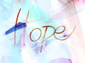 """Uno sfondo ideale per molteplici utilizzi. La scritta """"Hope"""", realizzata ad acquerello, si sovrappone allo sfondo con pennellate nei toni dell'azzurro, verde acqua, viola, rosa e marrone."""