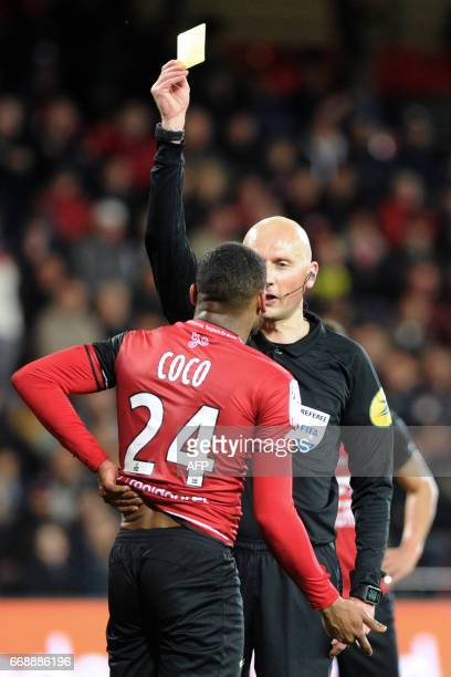 sFrench main referee Philippe Jeanne shows a yellow card to Guingamp's French defender Marcus Coco during the French L1 football match between...