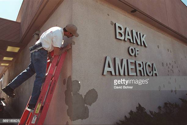 SFShoot100301DB Workman Gilbert Diaz of Van Nuys patches bullet holes in the Bank of America wall that were sustained during the Friday morning armed...