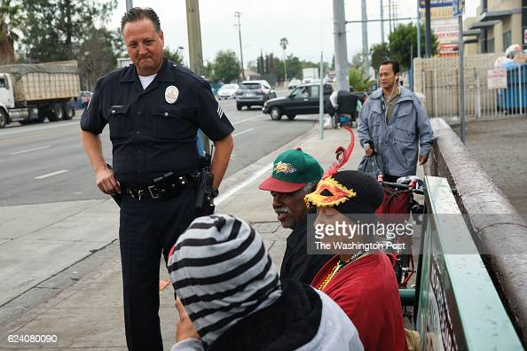 Sgt Charles Coleman of the LAPD Foothill Division speaks with Clarance Dolberry center right and Veronica De Leon right on the corner of the Van Nuys...