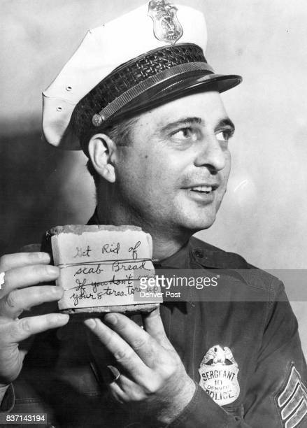 Sgt Clifford Stanley head of the police department's labor relations bureau holds the portion of a brick that was hurled through a plate glass window...