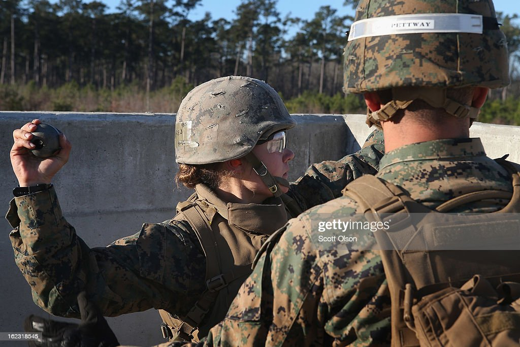 Sgt. Daniel Pettway (L) of Jacksonville, NC teaches Pvt. Erica Grenier of Two Rivers, Wisconsin the proper technique for throwing a hand grenade during Marine Combat Training (MCT) on February 21, 2013 at Camp Lejeune, North Carolina. Since 1988 all non-infantry enlisted male Marines have been required to complete 29 days of basic combat skills training at MCT after graduating from boot camp. MCT has been required for all enlisted female Marines since 1997. About six percent of enlisted Marines are female.