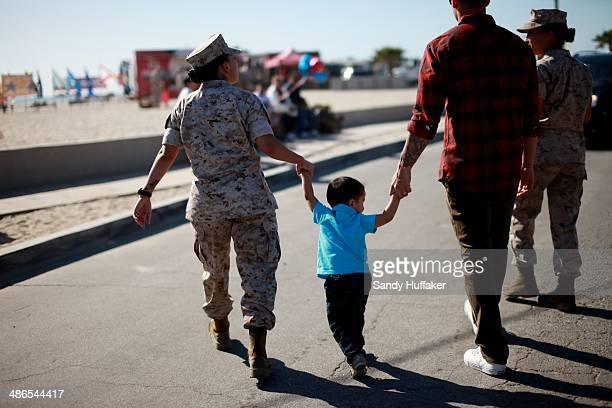 Sgt Didi Cruz walks with her Son Dominic and Husband Max during a homecoming at Del Mar Beach on April 24 2014 in Camp Pendleton California...