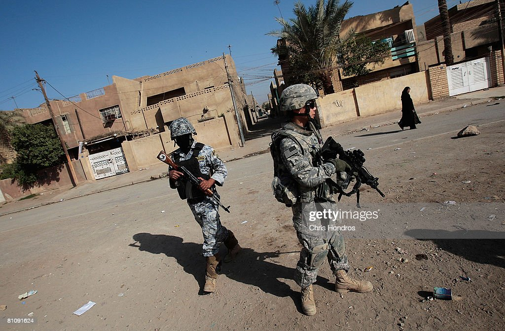 Sgt. Eric Chan of Staten Island, New York (R) of the 2nd Battalion, 30th Infantry Regiment of the 10th Mountain Division stands alongside an Iraqi National Police member (L) during a daytime joint patrol in Baladiyat neighborhood May 15, 2008 in Baghdad, Iraq. 10th Mountain soldiers take daily joint patrols with the Iraqi National Police, in the ongoing effort to build up stable national Iraqi security institutions aligned with the national government.