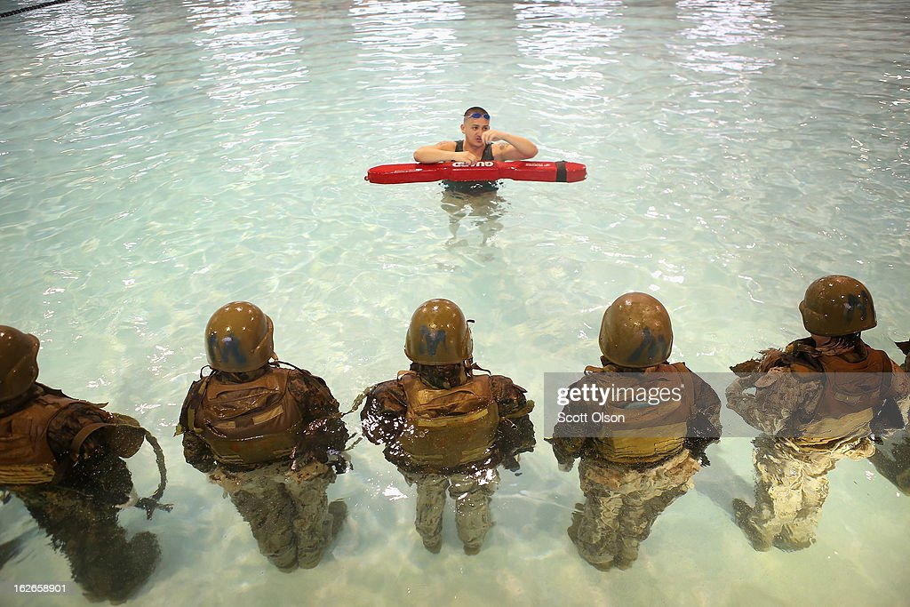 Sgt. Gustavo Ramos of Pomona, California teaches female Marine recruits to remove body armor while under water during boot camp February 25, 2013 at MCRD Parris Island, South Carolina. Male and female recruits are expected to meet the same standards during their swim qualification test. All female enlisted Marines and male Marines who were living east of the Mississippi River when they were recruited attend boot camp at Parris Island. About six percent of enlisted Marines are female.