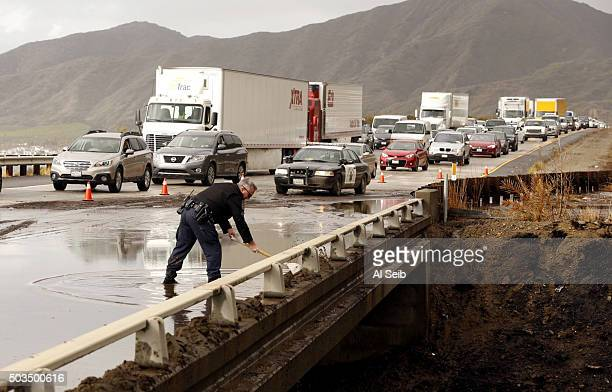 Sgt Joe Davy uses a shovel to try to clear a drain on the southbound lanes of the 101 Freeway after mud from the recent Solimar Fire flowed over the...