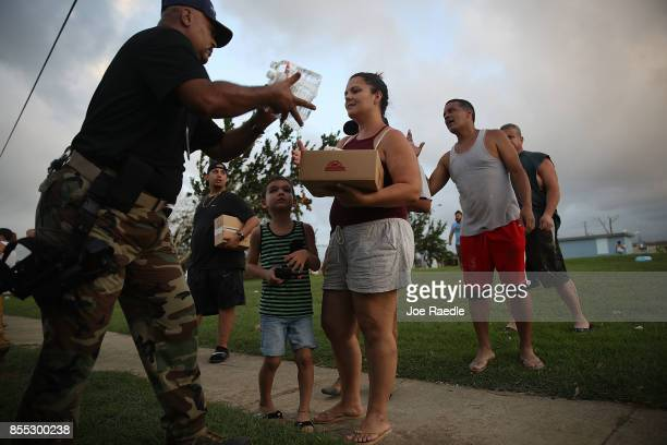 Sgt Nelson Sierra of the municipal police hands out food and water to hurricane survivors as he and volunteers deal with the aftermath of Hurricane...
