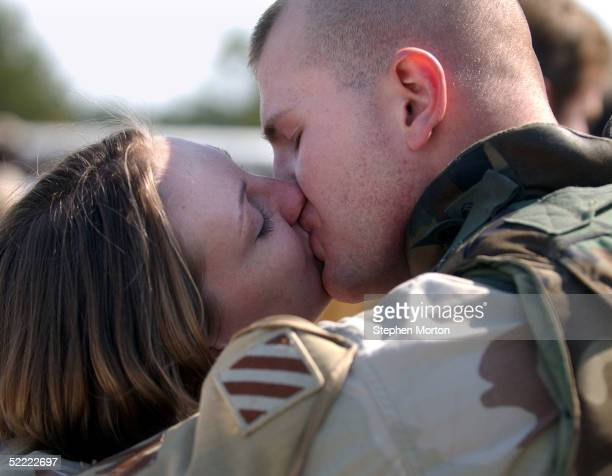 Sgt William Frizzell kisses his wife Amy February 20 2005 during a homecoming celebration for 150 soldiers from the Army's 3rd Infantry Division...