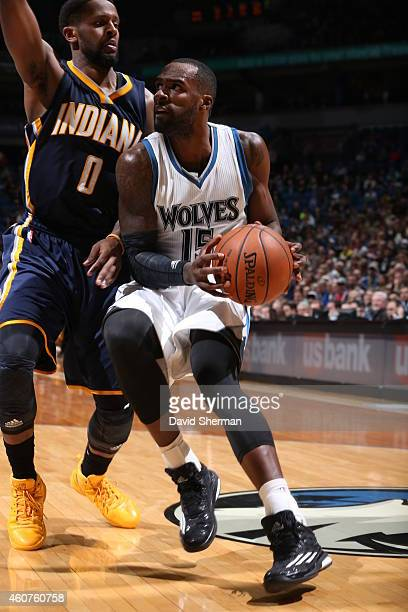 Shabazz Muhammad of the Minnesota Timberwolves drives to the basket against CJ Miles of the Indiana Pacers on December 21 2014 at Target Center in...