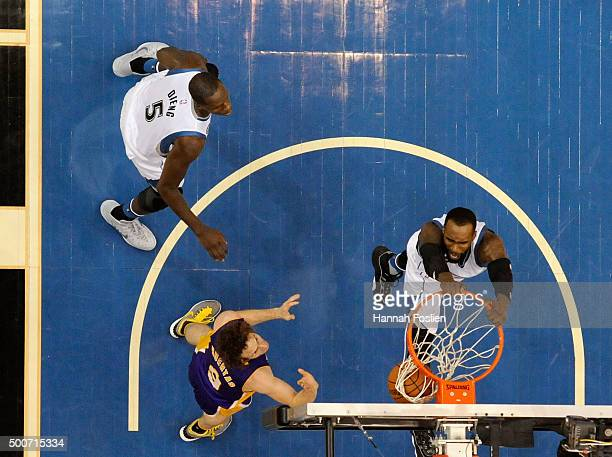 Shabazz Muhammad of the Minnesota Timberwolves hangs on the rim as teammate Gorgui Dieng and Marcelo Huertas of the Los Angeles Lakers look on during...