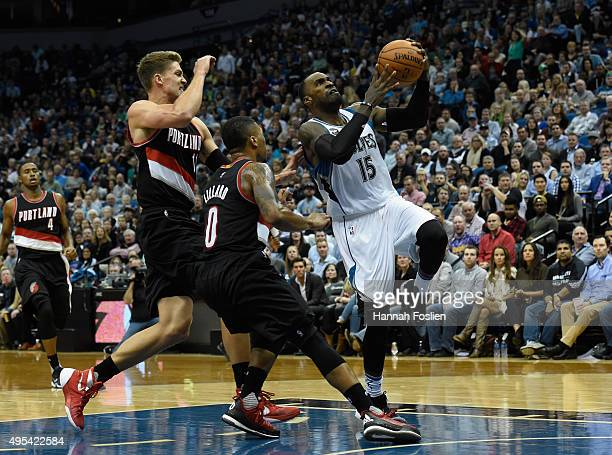 Shabazz Muhammad of the Minnesota Timberwolves shoots a basket against Mason Plumlee and Damian Lillard of the Portland Trail Blazers during the...