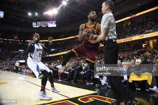 Shabazz Muhammad of the Minnesota Timberwolves watches as Kyrie Irving of the Cleveland Cavaliers collides with referee Ed Malloy as he falls out of...
