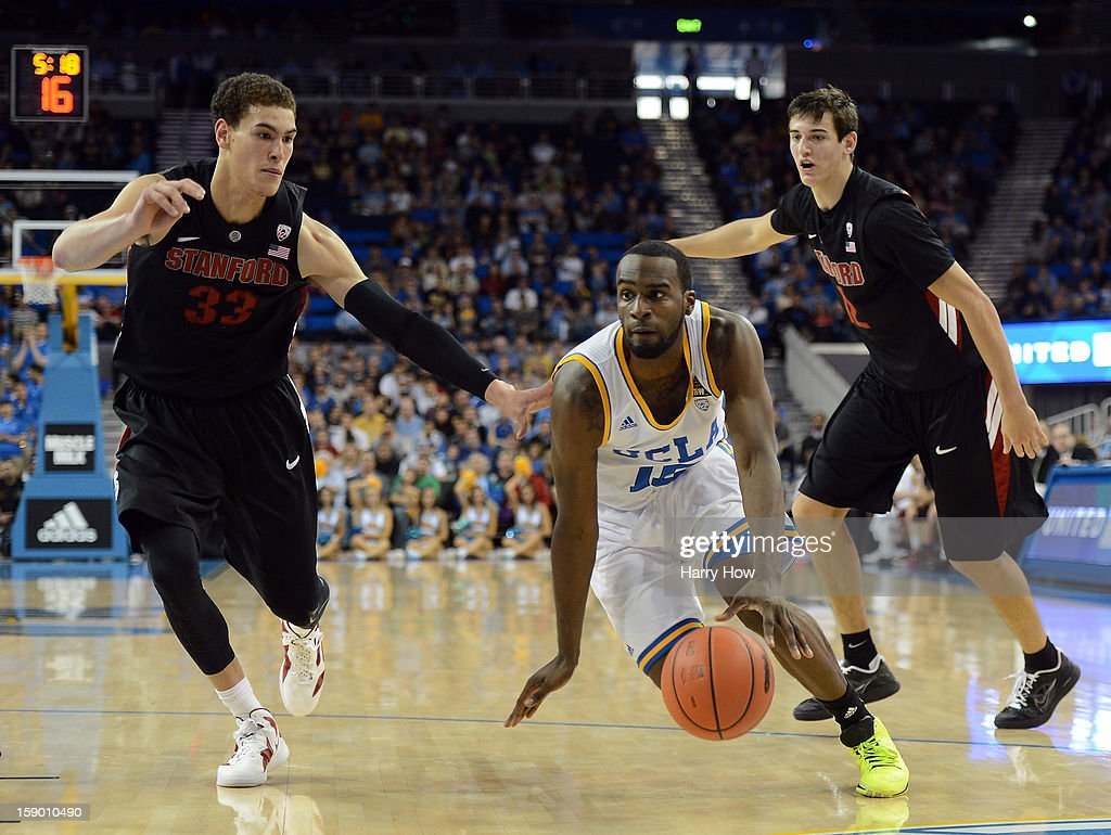 Shabazz Muhammad #15 of the UCLA Bruins dribbles by Dwight Powell #33 and Rosco Allen #12 of the Stanford Cardinal during a 68-60 UCLA win at Pauley Pavilion on January 5, 2013 in Los Angeles, California.