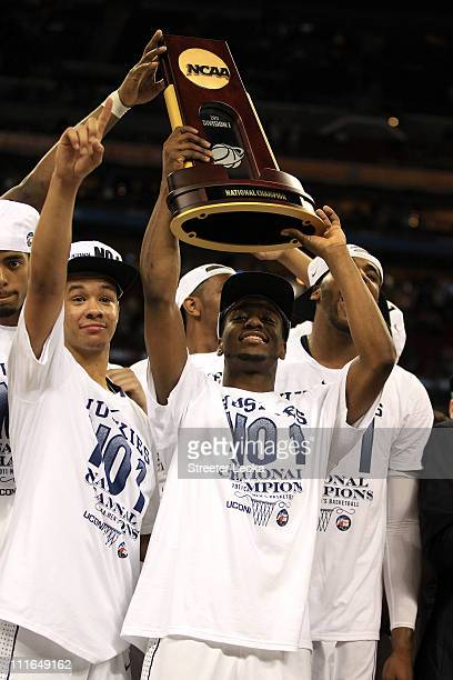 Shabazz Napier and Kemba Walker of the Connecticut Huskies celebrate with the trophy after defeating the Butler Bulldogs to win the National...