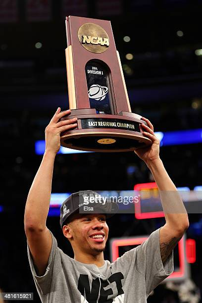 Shabazz Napier of the Connecticut Huskies celebrates with the trophy after defeating the Michigan State Spartans to win the East Regional Final of...