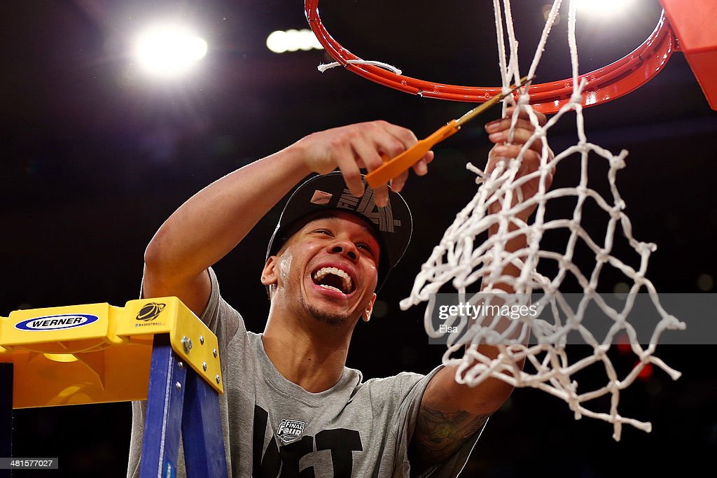 Shabazz Napier of the Connecticut Huskies cuts down the net after defeating the Michigan State Spartans to win the East Regional Final of the 2014...