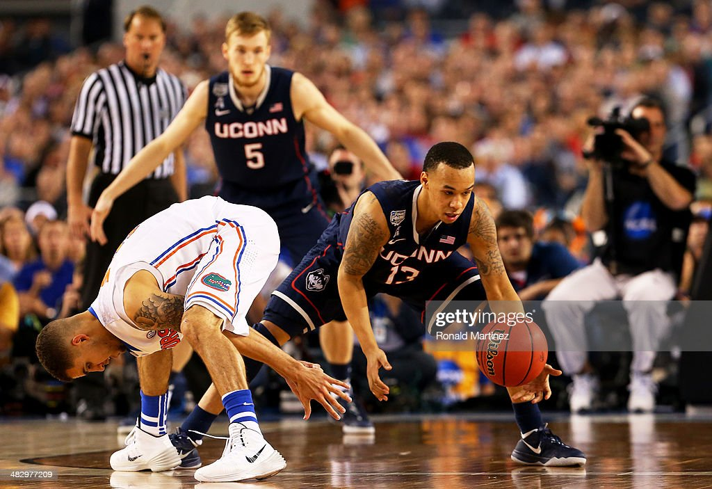 Shabazz Napier of the Connecticut Huskies picks up the ball from Scottie Wilbekin of the Florida Gators during the NCAA Men's Final Four Semifinal at...