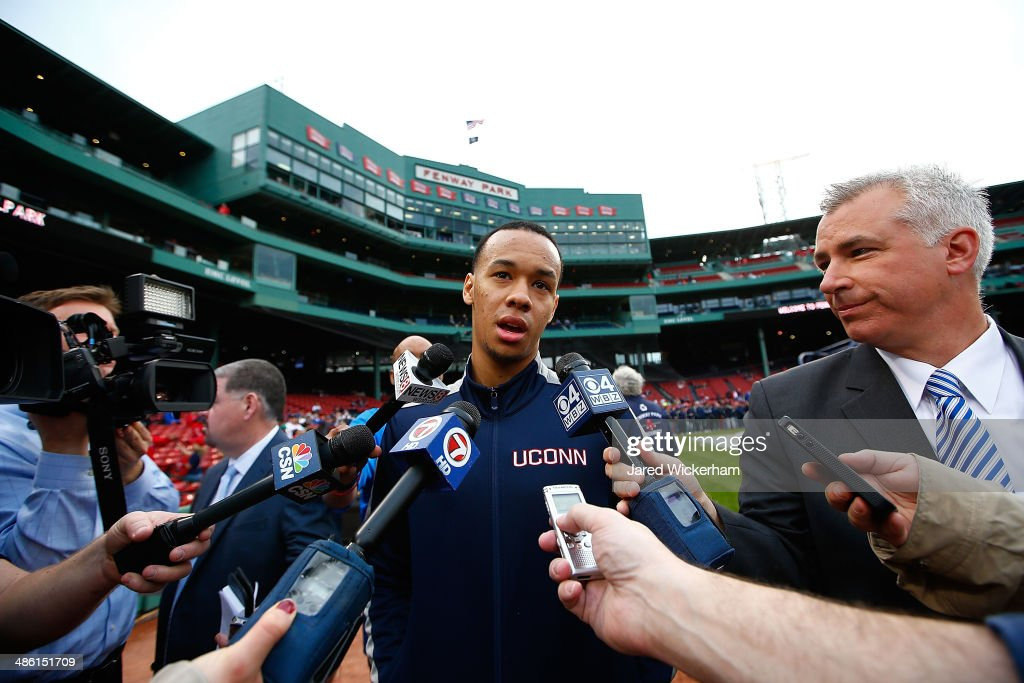 Shabazz Napier #13 of the national champion Connecticut Huskies answers questions from reporters prior to the game between the Boston Red Sox and the New York Yankees at Fenway Park on April 22, 2014 in Boston, Massachusetts.
