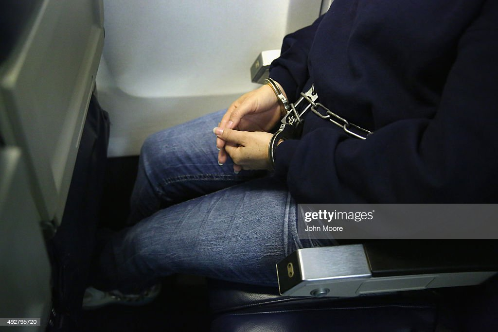 A shackled undocumented immigrant sits on an Immigration and Customs Enforcement charter jet early on October 15 2015 in Mesa Arizona The immigrants...