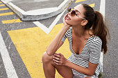 Sunglasses girl in street, looking away