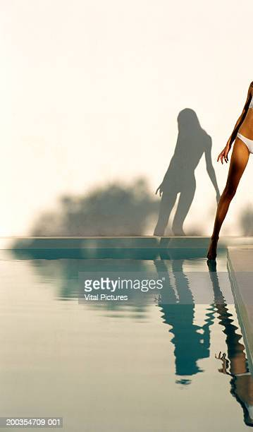 Shadow and reflection of woman in bikini dipping toe in swimming pool